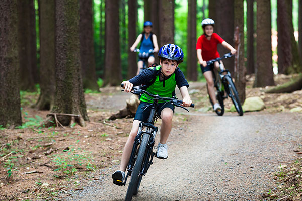 children biking in a trail