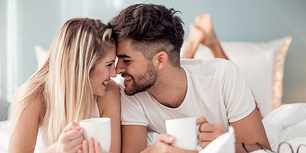 happy couple drinking coffee in bed